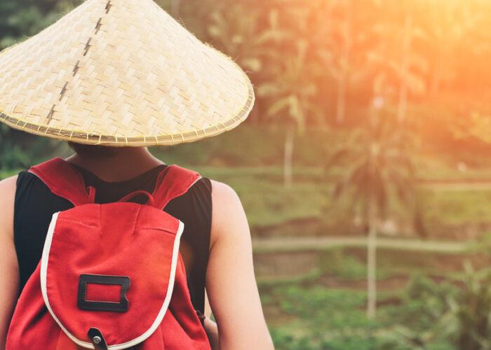 Jeune femme avec un chapeau et sac à dos traditionel de l'Asie